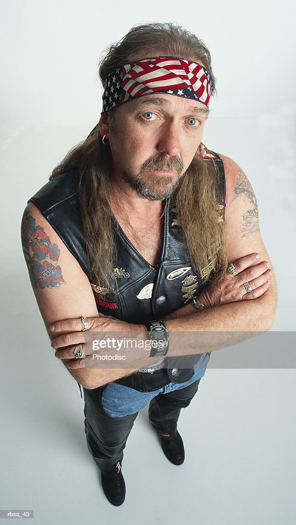 middle aged caucasian adult male with an earring and  long hair and a tatoo on both arms wears an american flag headband and a leather vest with motorcycle symbols as he folds his arms and looks up at the camera with an impudent expression : Foto de stock