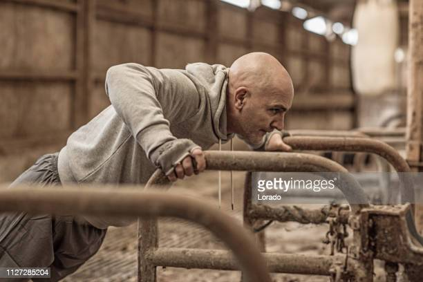 middle aged caucasian fighter working out in an abandoned farm - masculinity stock pictures, royalty-free photos & images