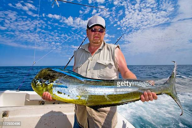 middle aged caucasian fisherman with mahi-mahi, dorado or dolphin fish - big game fishing stock photos and pictures