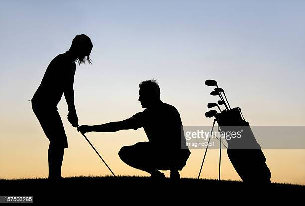 Middle Aged Caucasian Man Giving A Woman Golf Lesson