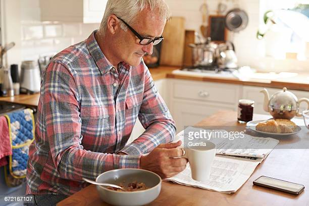 middle aged caucasian man reading newspaper at breakfast - einzelner mann über 40 stock-fotos und bilder