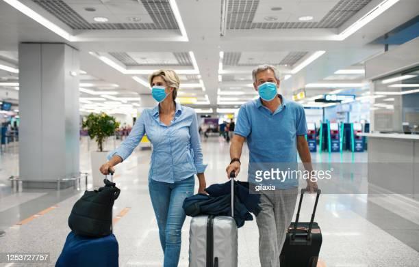 middle aged couple at an airport during coronavirus pandemic. - só adultos imagens e fotografias de stock