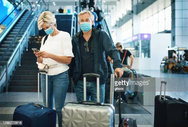 middle aged couple at an airport during coronavirus pandemic. - mid adult men stock pictures, royalty-free photos & images