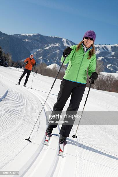 middle aged couple back country nordic skiing - nordic skiing event stock pictures, royalty-free photos & images