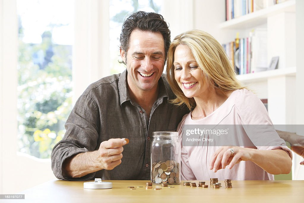 Middle aged couple counting coins : Stock Photo