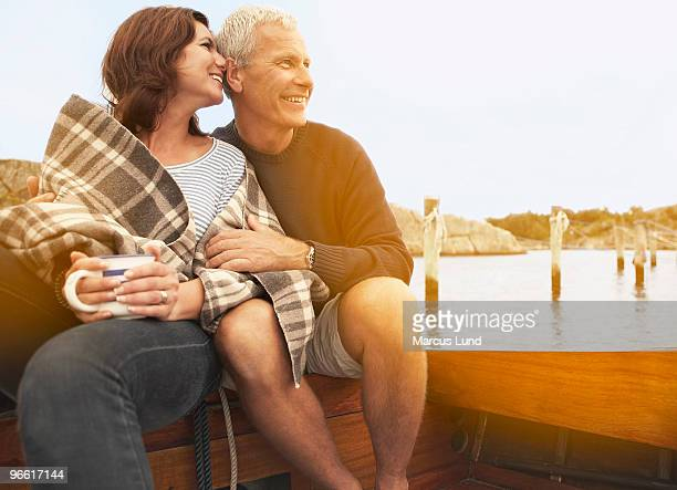 Middle aged couple cuddling on old boat