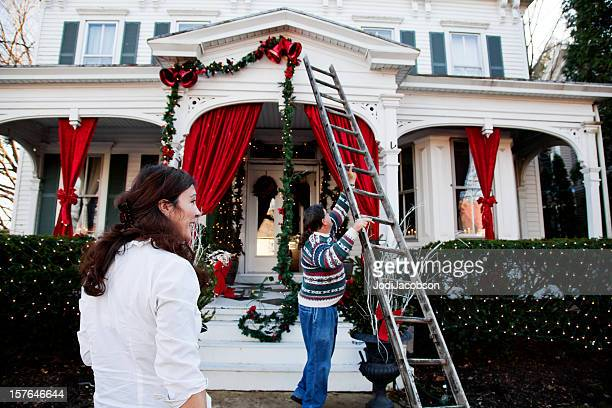 middle aged couple decorating for the holidays - hanging stock pictures, royalty-free photos & images