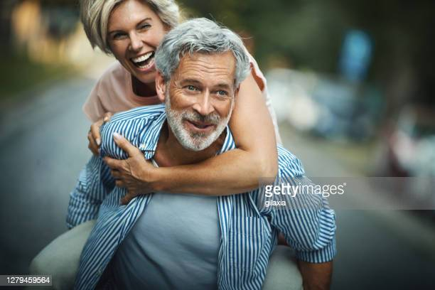 middle aged couple having fun outdoors. - 45 49 years stock pictures, royalty-free photos & images