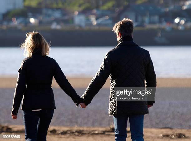 Middle aged couple holding hands, Devon, UK.