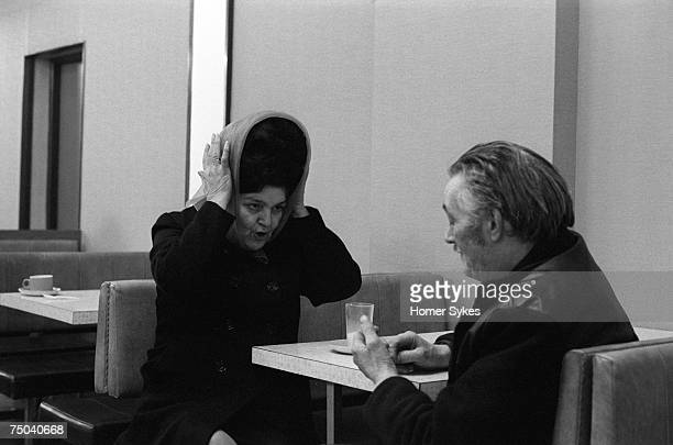 A middle aged couple in a cafe in Waterloo South London 1974 The woman has a beehive hairstyle under a headscarf