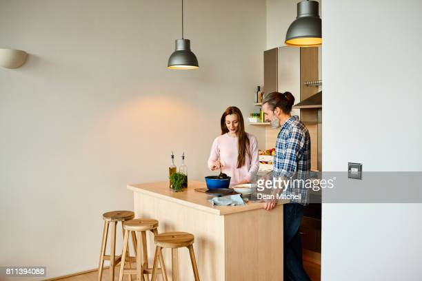 middle aged couple in kitchen preparing lunch - dean foods stock photos and pictures