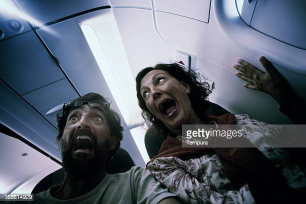 Middle aged couple in terror on a plane.