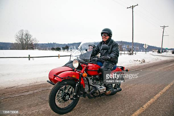 A middle aged couple on a road-trip on a motorycle