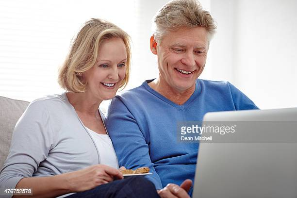 Middle aged couple using laptop smiling