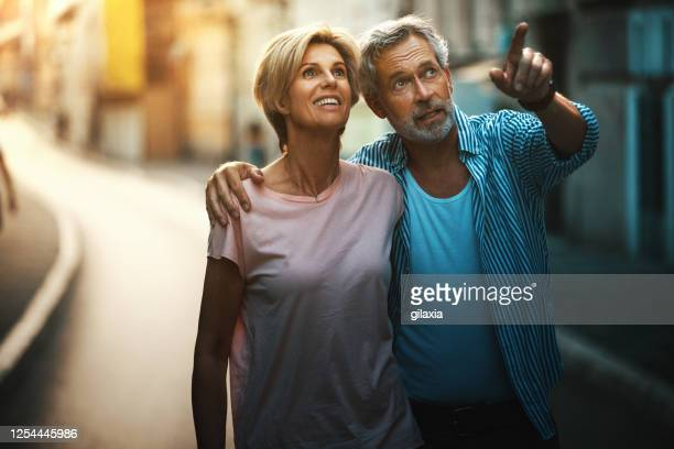 middle aged couple walking in a city street. - mid adult couple stock pictures, royalty-free photos & images