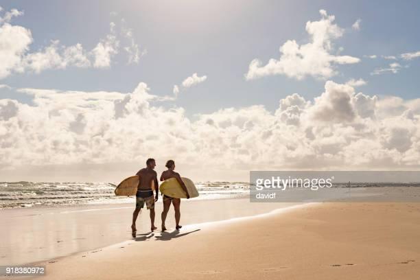 applying paar mit malibu longboard surfboards - bundesstaat new south wales stock-fotos und bilder