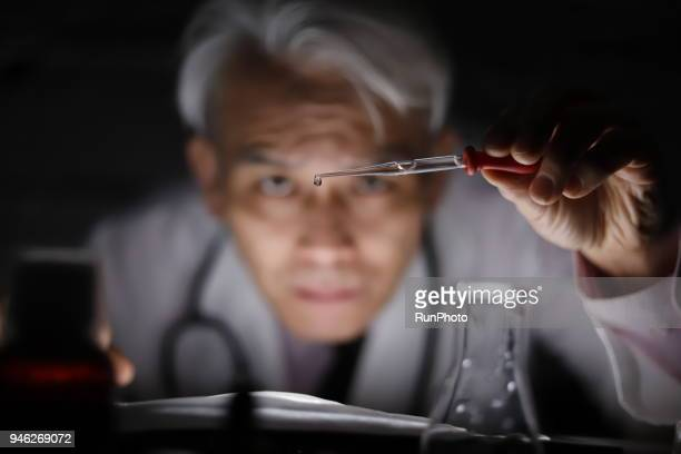 middle aged doctor dropping liquid with pipette - concentration stock pictures, royalty-free photos & images