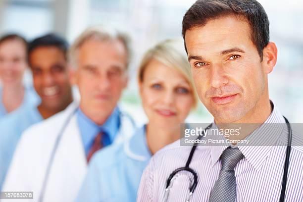 Mittleren Alter Arzt steht vor seinem team