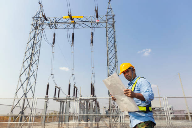 Middle aged Engineer reading document data or blueprint for inspect quality control Efficiency Wind turbine for generating electric power, renewable energy, clean energy or environment conservation concept.