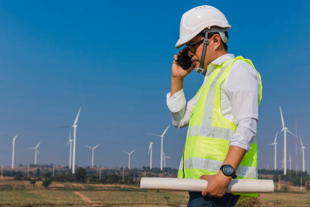 Middle aged Engineer talking walkie-talkie with co-worker for inspect quality control Efficiency Wind turbine for generating electric power, renewable energy, clean energy or environment conservation concept.