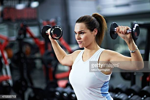 Middle Aged Female Lifting Weights in Gym