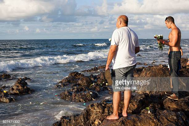 Middle aged male Brazilians standing by the sea in contemplation and prayer making offerings of flowers to Yemanja the Orixa goddess of the Sea and...