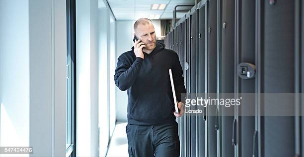 Middle aged male technical employee working in server room