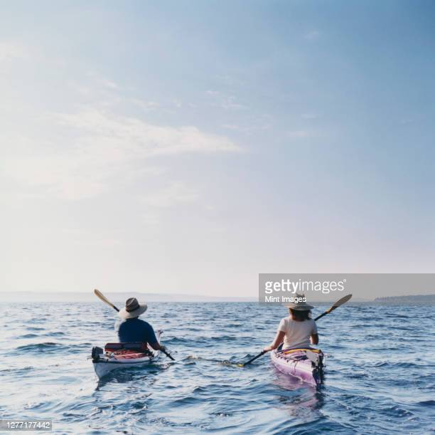 middle aged man and woman sea kayaking on calm waters - sea kayaking stock pictures, royalty-free photos & images