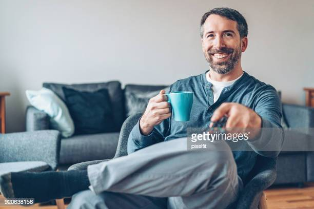 middle aged man drinking coffee and watching tv - changing channels stock photos and pictures