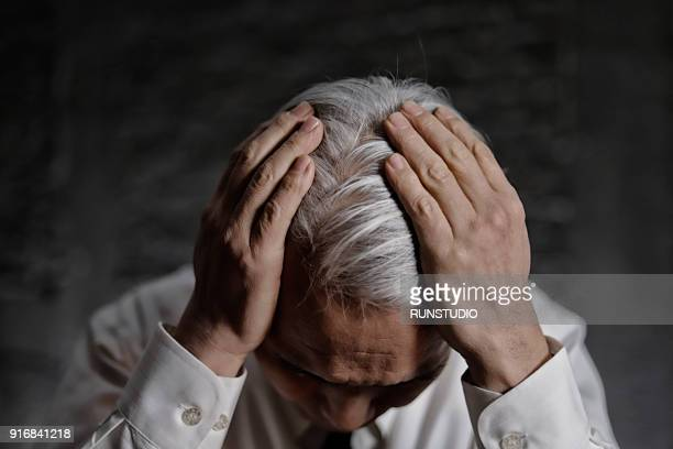 middle aged man holding head in pain and despair - touching stock photos and pictures