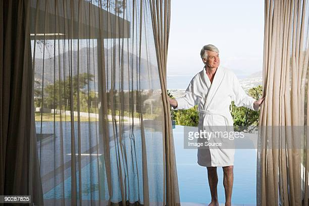 Middle aged man in robe pulling back poolside curtains