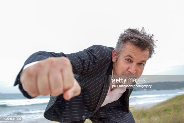 middle aged man in suit throwing punch at camera - solo un uomo maturo foto e immagini stock