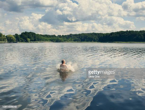 Middle aged man jumping  into lake