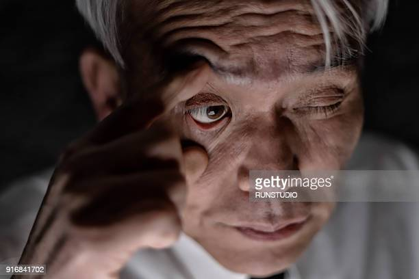 Middle aged man opening eye with fingers