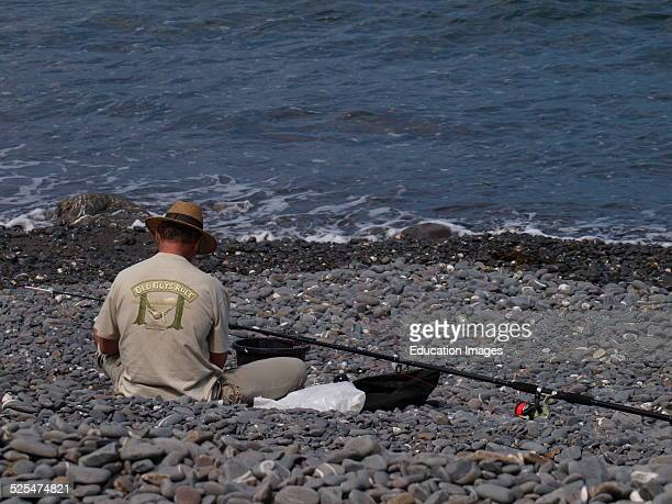 Middle aged man preparing fishing rod on the beach Millock Bude Cornwall UK
