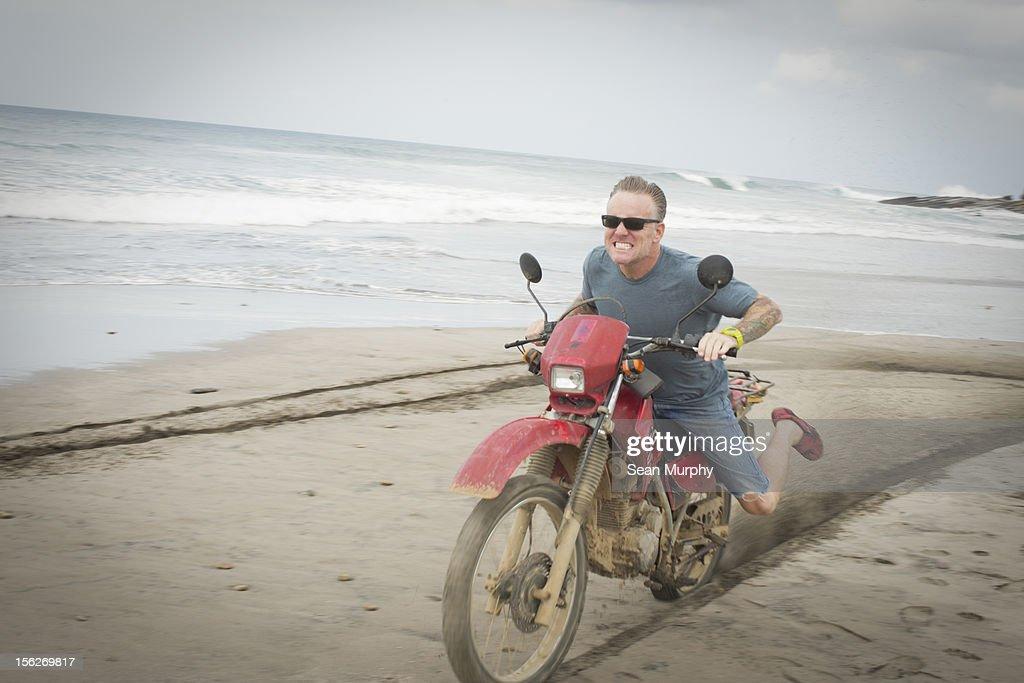 Middle Aged Man Ridding A Motorcycle on a Beach : Bildbanksbilder