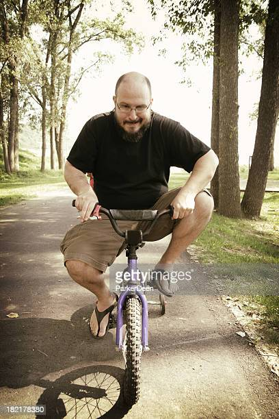 Middle Aged Man Rides Very Small Bicycle