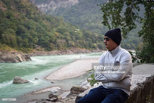 Middle Aged Man Sitting Alone Riverside and Looking at river Ganga, Rishikesh