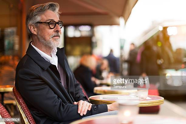 middle aged man sitting in a french terrace. - millionnaire stock photos and pictures