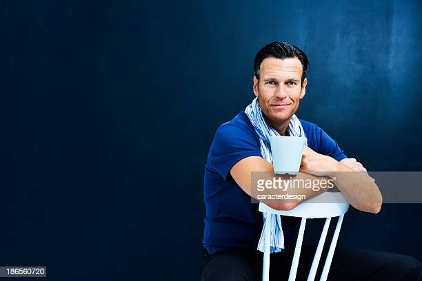 middle aged man sitting on white chair - 40 49 jaar stockfoto's en -beelden