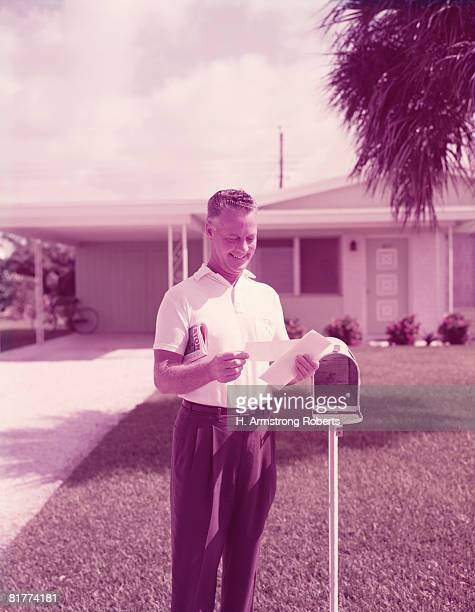 Middle aged man smiling, reading mail by mailbox, outside front of house. (Photo by H. Armstrong Roberts/Retrofile/Getty Images)