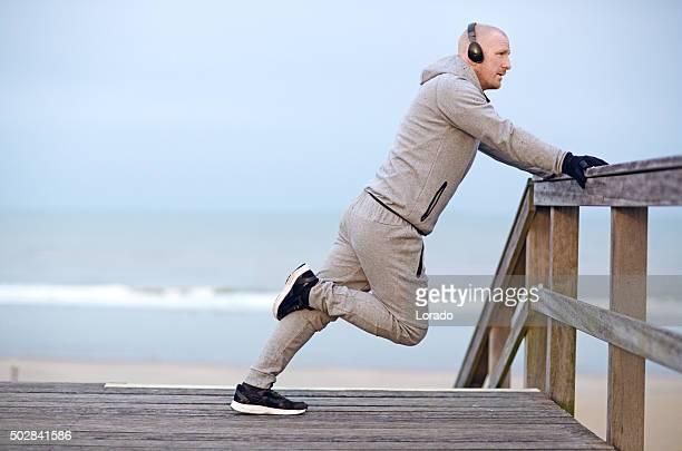 Milieu homme âgé un étirement sur la plage le matin d'hiver
