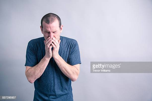 A middle aged man suffering from flu symptoms
