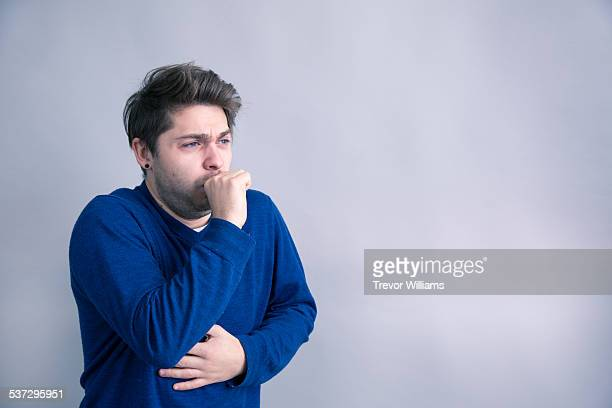 a middle aged man suffering from flu symptoms - cough stock photos and pictures