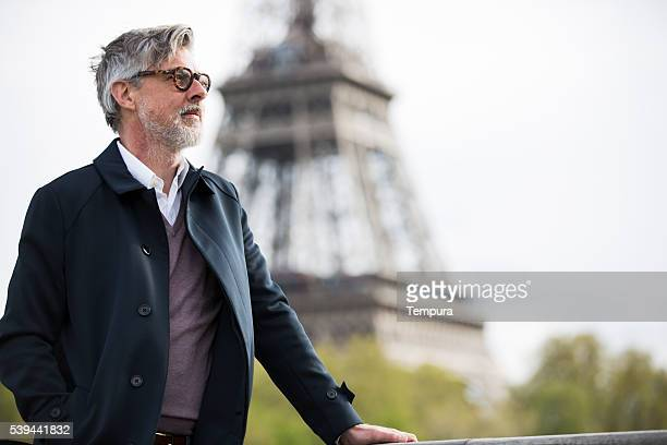 Middle aged man traveling near the eiffel tower.