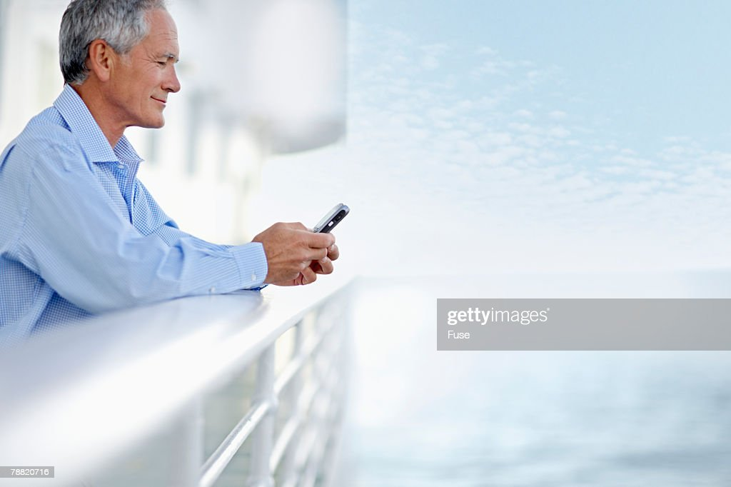 Middle Aged Man Using A Cell Phone On A Cruise Ship Stock Photo - Using a cellphone on a cruise ship
