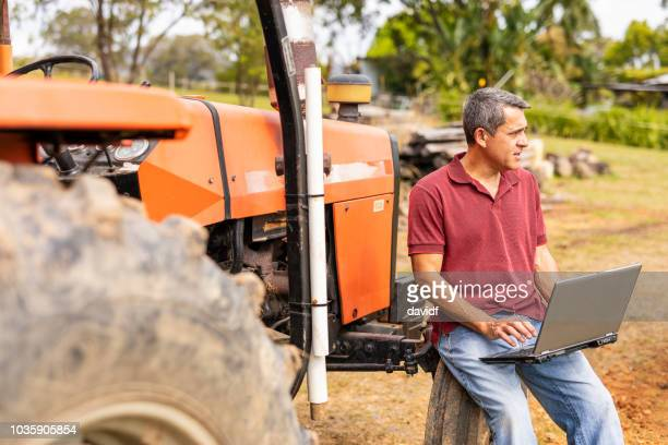 middle aged man using a laptop computer on his farm - one mature man only stock pictures, royalty-free photos & images