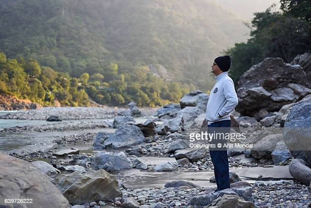 Middle Aged Man Walking At Riverbank In Forest Surrounded Mountain Area at Ganga, Rishikesh