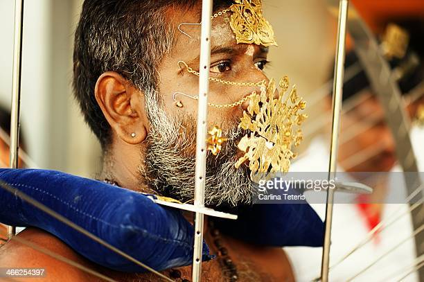 CONTENT] A middle aged man wearing a kavadi with mulitiple facial piercings concentrates as he walks during Taipusam festival honouring the Hindu God...