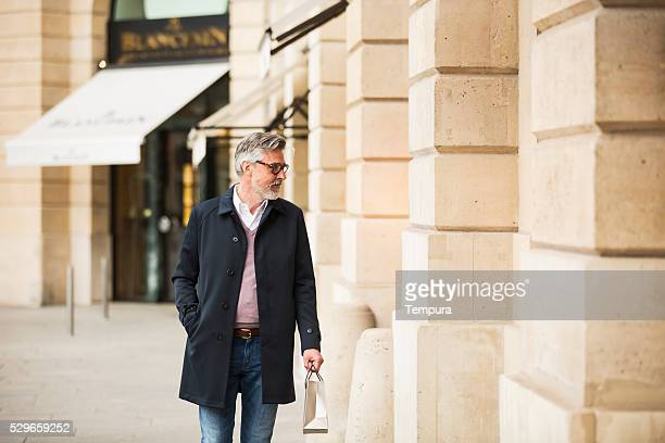 middle aged man window shopping in paris center. - millionnaire stock photos and pictures